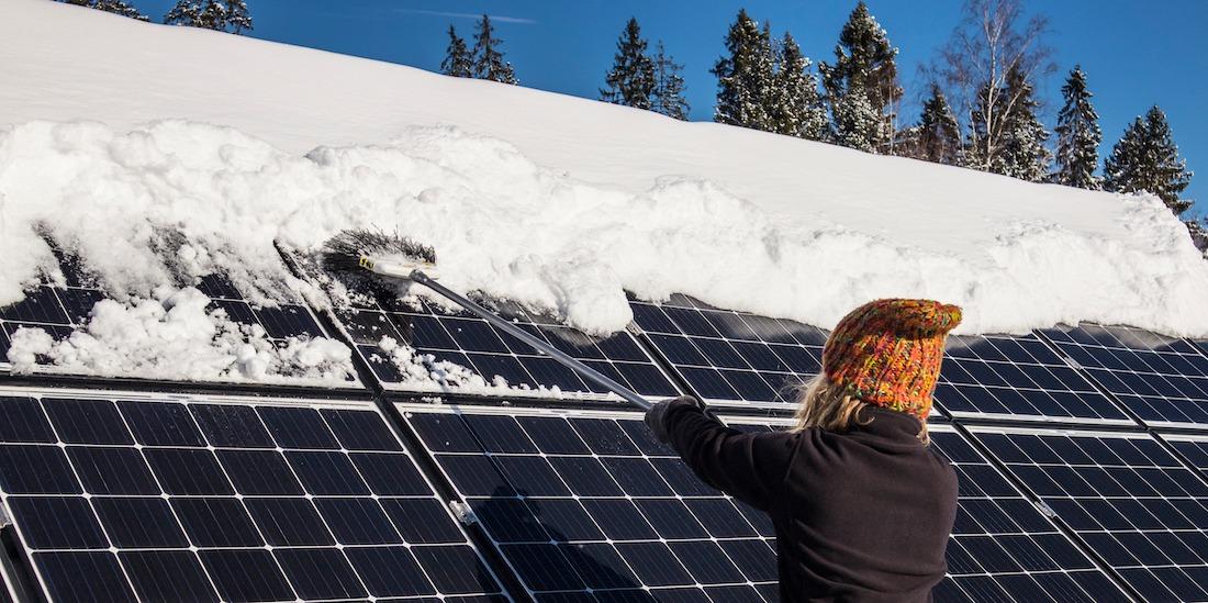 kvinna borstar bort snö från solpaneler på vintern